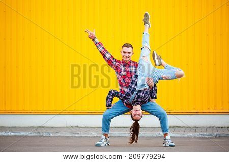 Fine horisontal portrait of carefree young couple dancing holding hands in street and smiling, enjoying life