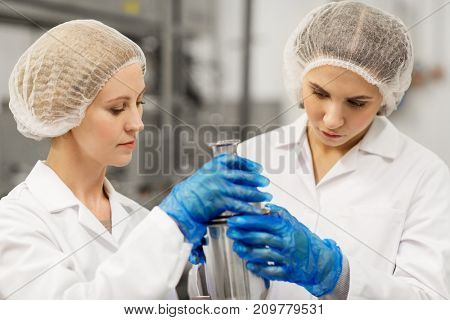 manufacture, industry, production and people concept - women technologists working at ice cream factory and assembling product dispenser together