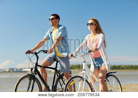 people, leisure and lifestyle concept - happy young couple riding bicycles on beach