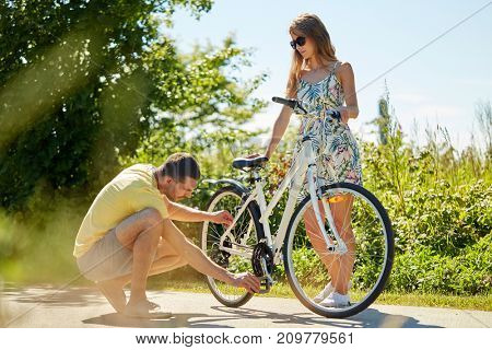 people, leisure and lifestyle concept - young couple fixing bicycle on country road