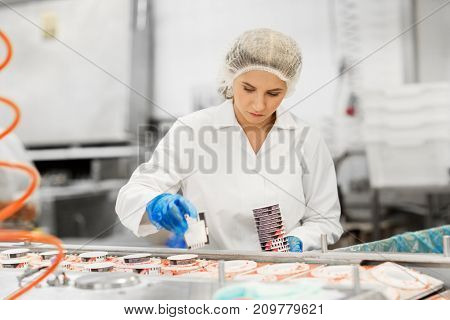 industry, food production and people concept - woman working at ice cream factory conveyor