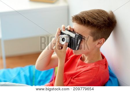 hobby, technology and people concept - happy boy with film camera photographing at home