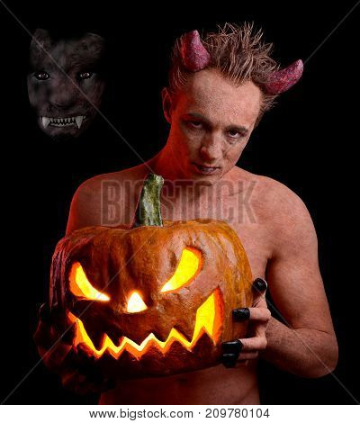 Man in the guise of the devil and with a pumpkin in his hands. On the holiday of Halloween