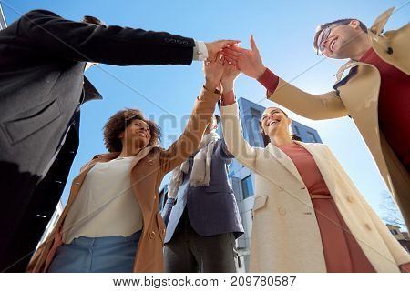 business, success and gesture concept - international group of people or students making high five on city street