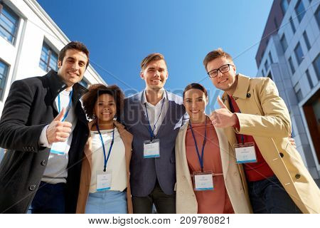 business, success and corporate concept - international group of people with name tags or conference badges showing thumbs up on city street