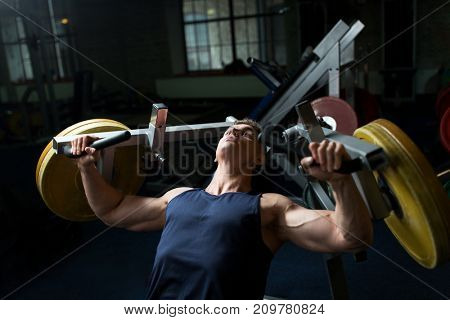 sport, fitness, bodybuilding and people concept - man doing chest press on exercise machine in gym