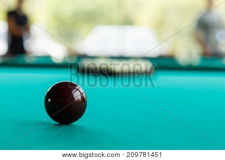 Dark red or black ball on the green table cloth against the background of a blurry pyramid