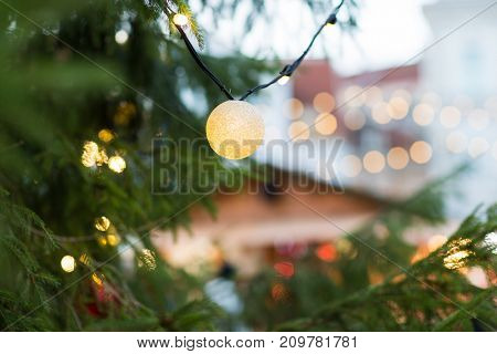 holidays and decoration concept - close up of christmas tree garland bulb outdoors