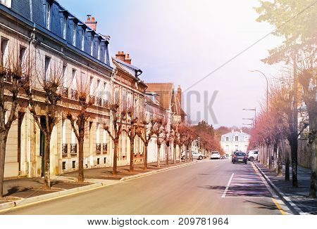 Romantic cityscape of Chantilly with old houses on both sides of road at sunny day, Oise, France