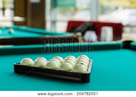 The collected pyramid of balls on the green leaf of the table in the triangle on the table
