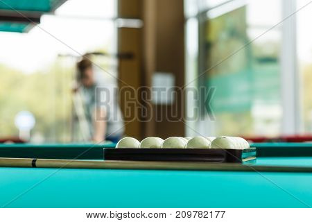 The collected pyramid of balls on a green table cloth in a triangle on a table with cues