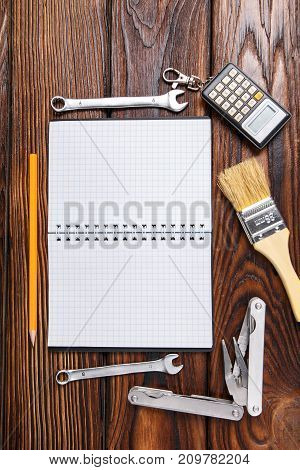 Set of old hand tools and notepad on wooden table