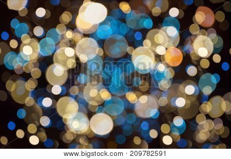 holidays and party concept - blue, yellow and black christmas background with blurred bokeh lights