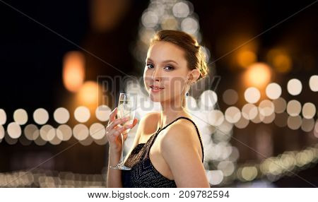 holidays, people and luxury concept - beautiful young asian smiling woman drinking non alcoholic champagne at party over christmas tree lights background