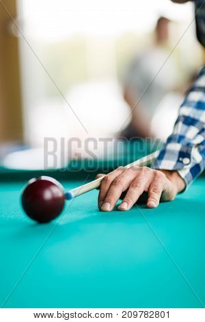 A player in a checkered shirt is about to break a pyramid with a red ball close up
