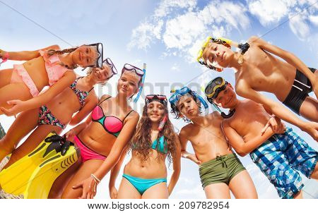 Group of many kids on the beach in swimsuits wearing scuba masks bending over and looking from above at camera