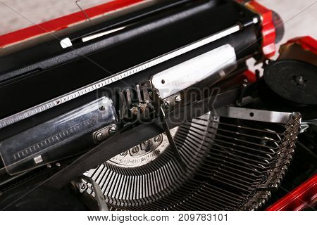 Red vintage typewriter maschine on the table. Close up image