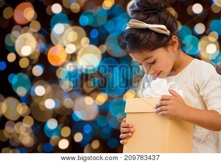 holidays, childhood and people concept - smiling little girl with gift box over lights background