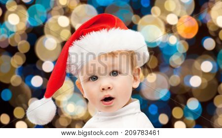 christmas, holidays and people concept - little baby boy in santa hat over lights background