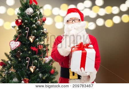holidays and people concept - man in costume of santa claus with gift box and christmas tree over lights background making hush gesture