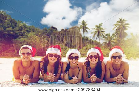 christmas, travel, winter holidays and people concept - group of friends in santa helper hats sitting over tropical seychelles island beach background