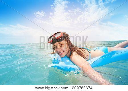 Teen girl having fun swimming on matrass in sea and snorkeling