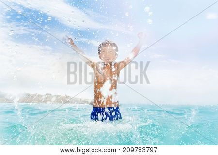 Little boys splashing in the sea on summer happy day