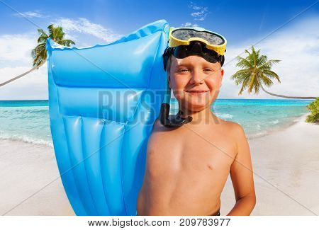 Happy kid in snorkeling mask standing with inflatable matrass on palm beach