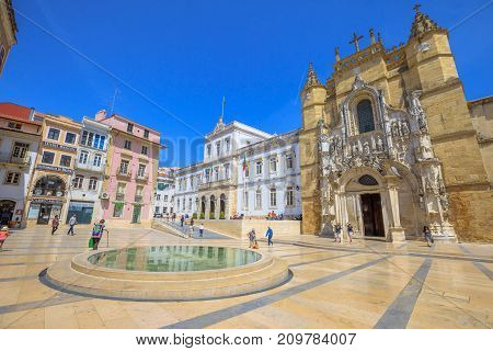 Coimbra, Portugal - August 14, 2017: people in historic square with popular Santa Cruz Monastery and Church and Town Hall. Sunny day with blue sky. Old Coimbra town in Central Portugal, Europe.