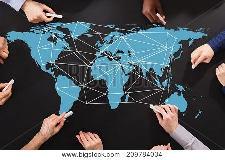 Elevated View Of Business People's Hand Drawing Lines On World Map Representing Global Business