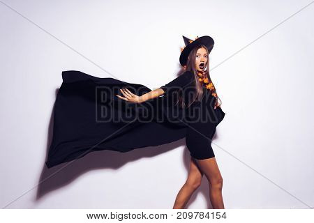 a young sexy gothic girl dressed in a witch for Halloween, standing in a big black hat, and a waving cloak, looks surprised