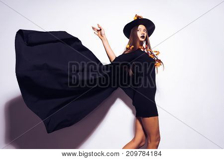 a young sexy gothic girl dressed in a witch for Halloween, standing in a big black hat, and a waving cloak