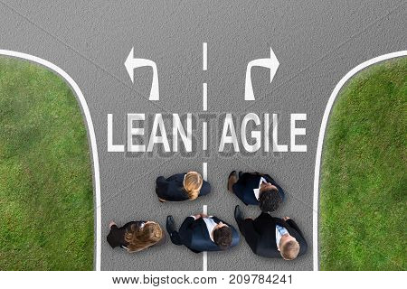 High Angle View Of Businesspeople Standing Near Arrows Showing Lean And Agile Directions