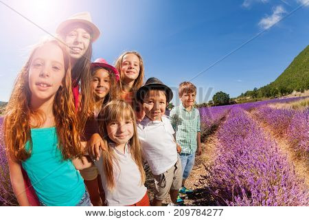 Close-up portrait of happy age-diverse boys and girls, standing in lavender field at sunny day
