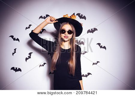 young sexy gothic girl dressed in a witch for Halloween, standing in a big black hat and sunglasses, smiling
