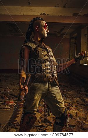 Mad actor of the post-apocalyptic world posing in the ruined building.