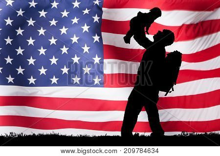 Silhouette Of A Soldier Carrying His Child In Front Of American Flag