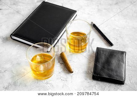 whiskey cocktails, cigar, wallet and notebook for men meeting on stone pub table background