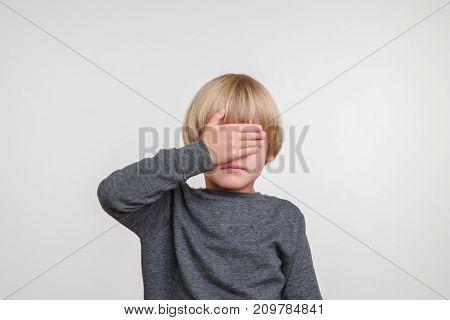 Fine portrait of caucasian boy. Handsome happy child, photo on grey background