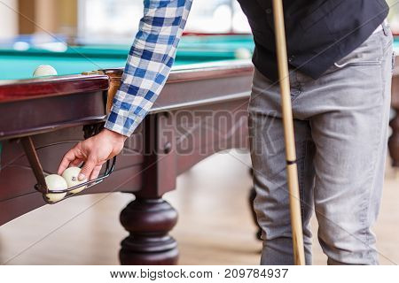 A player in a striped shirt pulls out a billiard ball from the paw of the table