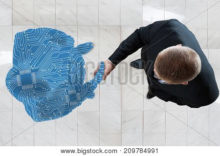 High Angle View Of Business Man Shaking Hands With Digital Generated Human Figure