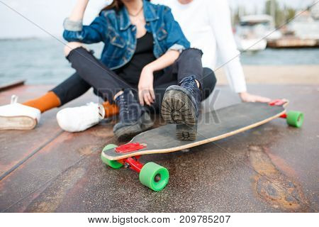 Happy couple in love hugging. Pretty girl and attractive man sitting near a skateboard. River on the background. Close-up of skateboard.
