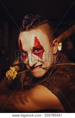 Mad raider with painted face and rose in his mouth preparing to fight
