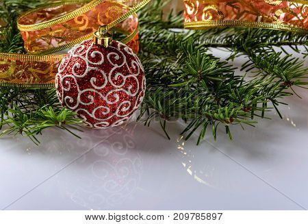 Christmas festive card with fir branches Christmas ball and festive decor on the white background . Space for an object.