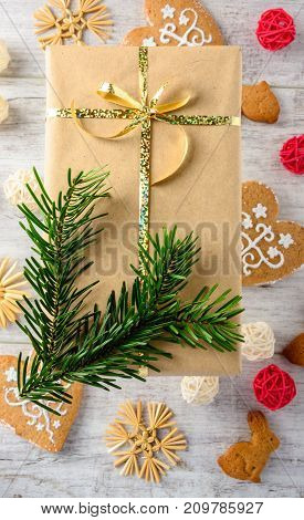 Christmas festive card with fir branches gift boxes and cakes on the white wooden background . Flat lay.