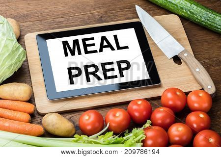 High Angle View Of Meal Preparation Text On Digital Tablet With Vegetables On Desk