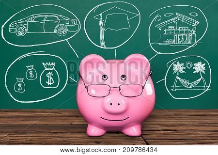 Piggy Bank With Spectacles Against Green Chalkboard