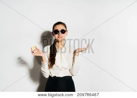 a young modern successful girl with glasses is holding a bank card and gold bitcoin