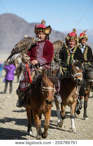 OLGIY, MONGOLIA - SEP 30, 2017: Kazakh Golden Eagle Hunter in traditional clothing, with a golden eagle on his arm during annual national competition with birds of prey