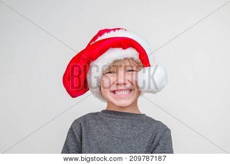 Horisontal emotional portrait of caucasian boy with santa hat. horizontal photo